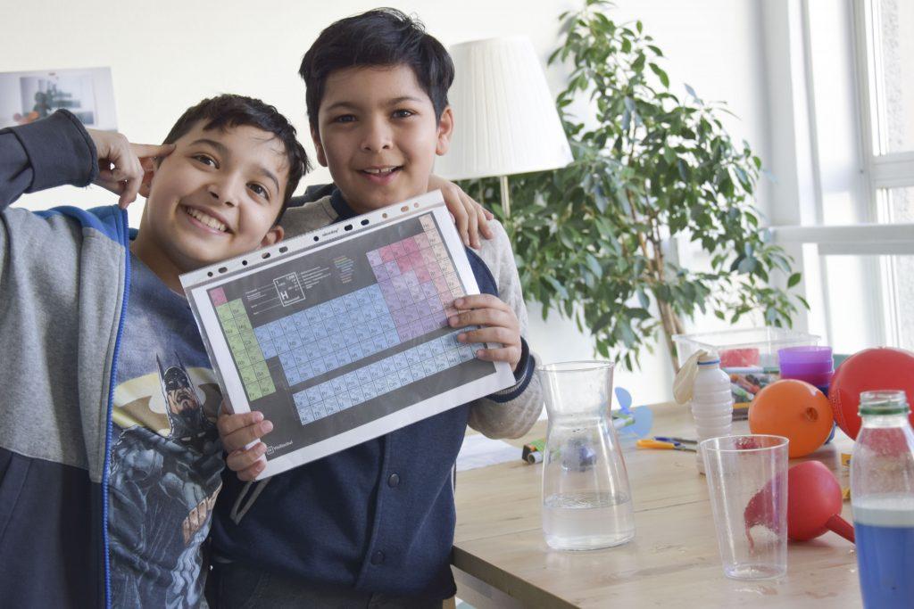Zwei grinsende Jungs stehen nebeneinander und halten eine Periodensystem hoch