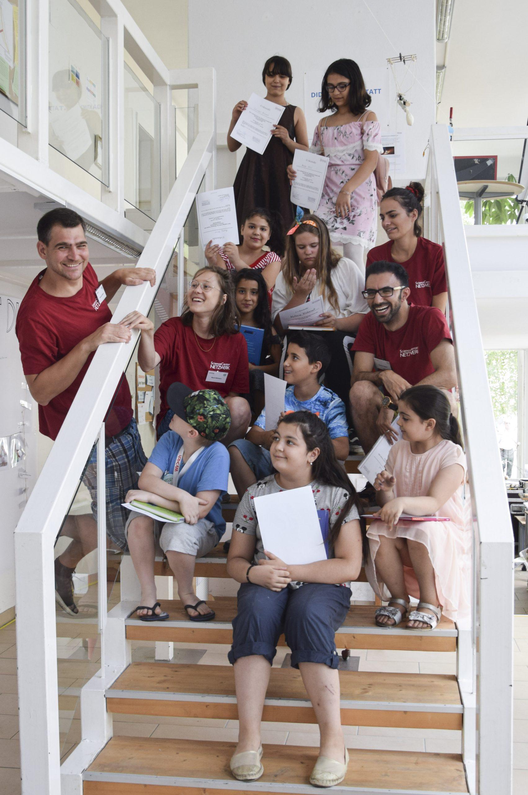 Ein Gruppenfoto auf der Stiege mit Betreuer und Kinder