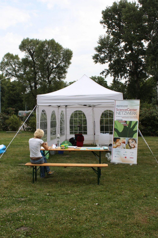 Zelt und Tisch mit Experimentiermaterialien im Park
