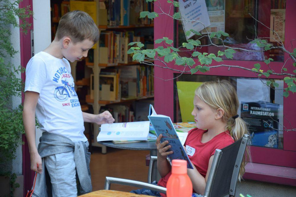 Zwei lesende Kinder im Hof der Bücherei