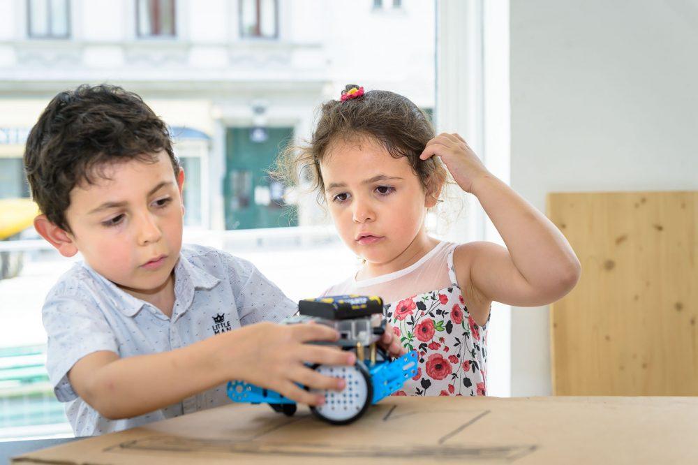 Kinder experimentieren mit einem Roboter